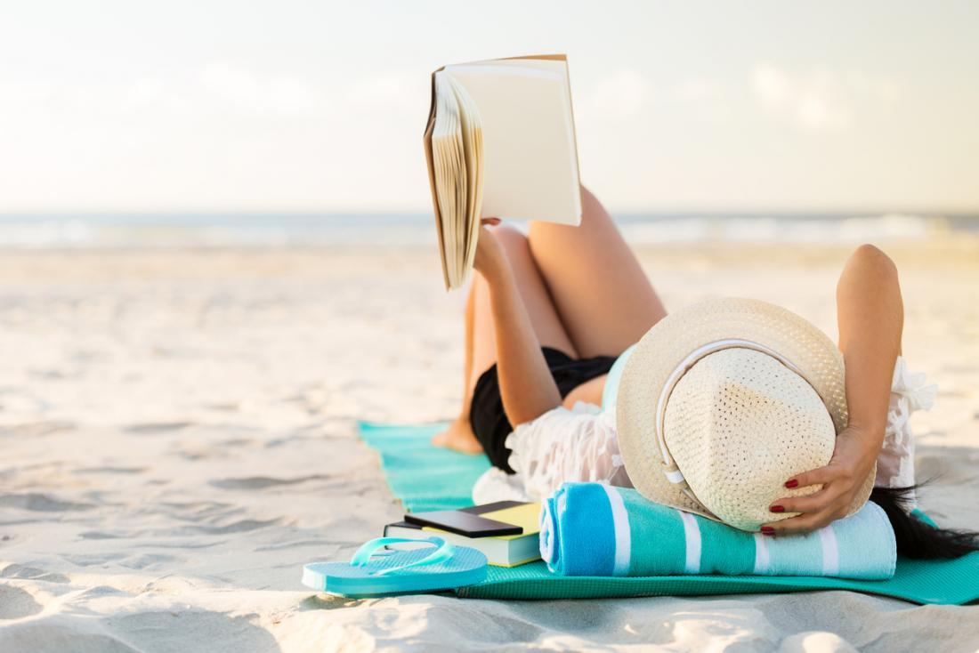 woman sunbathing and reading a book at the beach